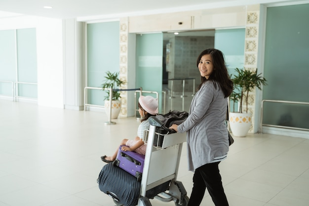 Asian mom looks at the camera while walking pushing the trolley