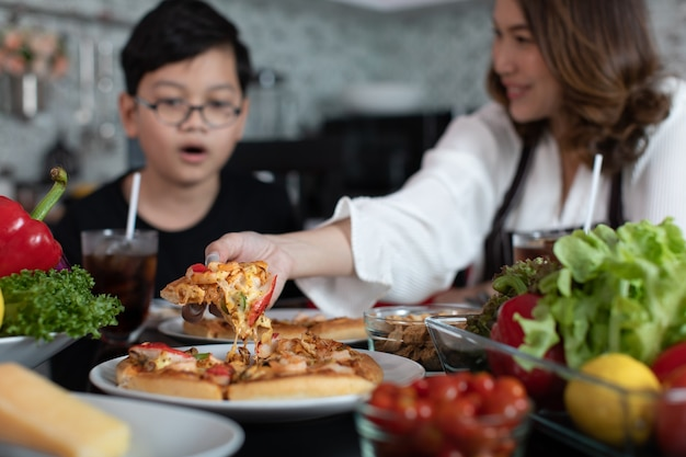 Asian mom and son sitting in home kitchen and eating homemade pizza together with various kinds of vegetables. idea for happiness of good time sharing in family.