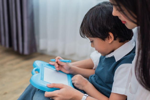 Asian mom teaching cute boy to drawing in chalkboard together. back to school and educatio