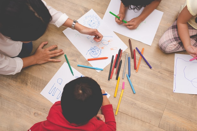 Asian mom teaching four little children to drawing art class with color pen
