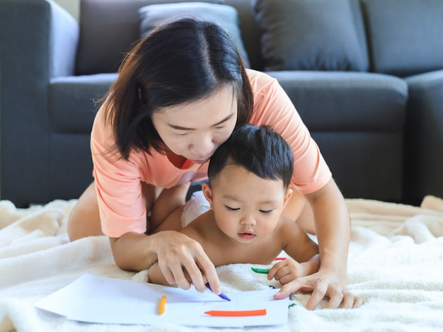 Asian mom teaching her baby boy draw