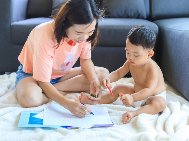 彼女の男の子を描くアジアのお母さんを描く