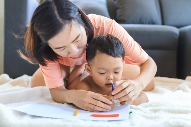 Asian mom teaching her cute baby boy to use crayons to draw on paper at home. family and togetherness concept.