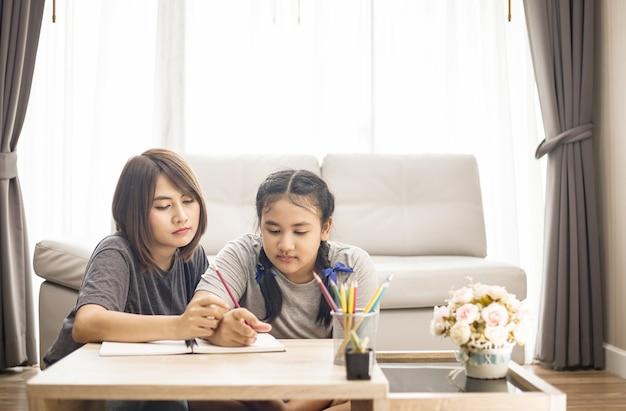 自宅で娘のために宿題を教えるアジアのお母さん