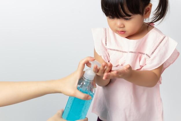 アジアのママが赤ちゃんの手を掃除するためにアルコール消毒ジェルを使用しています。コロナウイルス消毒