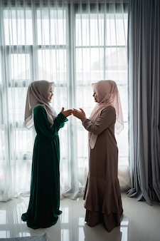 Asian moslem woman say salam when meeting her friend