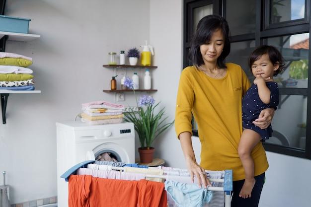 アジア人の母親、主婦が赤ちゃんを運んでいる間、自宅の洗濯室で衣類を乾かして吊るす