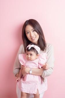 아시아 어머니와 사랑스러운 아기 소녀는 분홍색 벽에 행복