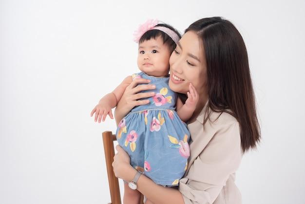 아시아 어머니와 사랑스러운 아기 소녀는 흰 벽에 행복