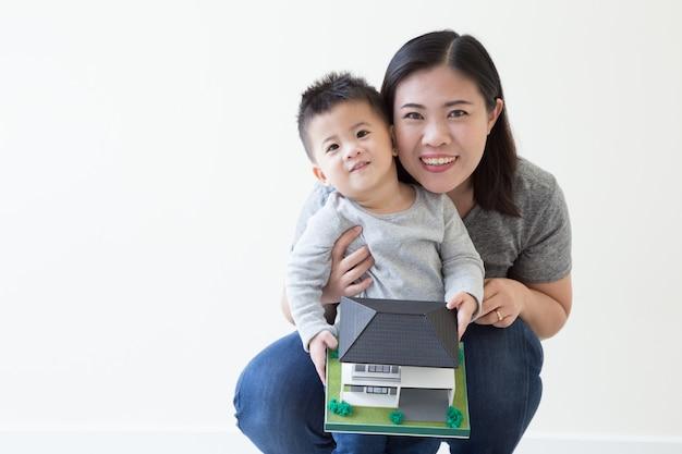 Азиатские мать и ребёнок усмехаясь и держа домашнюю модель, концепцию недвижимости займа