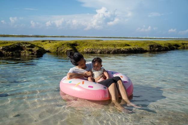 アジアの母親と赤ちゃんがビーチでゴム製リングフロートに乗る