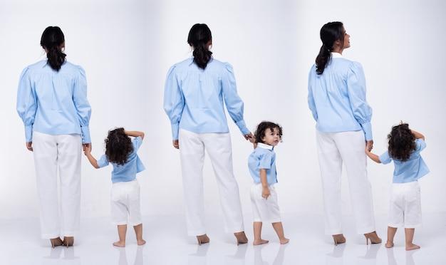 Азиатская мать и кавказская дочь вместе носят одно и то же синее платье. маленькая девочка держит маму за руку и улыбается с любовью. белый фон изолированные