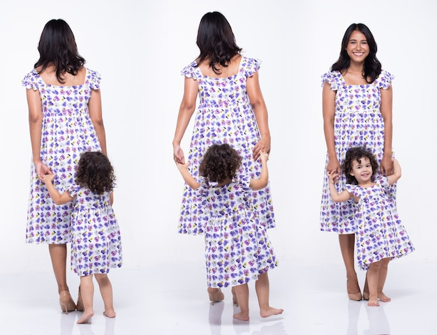 Азиатская мать и кавказская дочь вместе носят одно и то же платье с блузкой с пурпурным цветком. маленькая девочка держит маму за руку и улыбается с любовью. белый фон изолированные