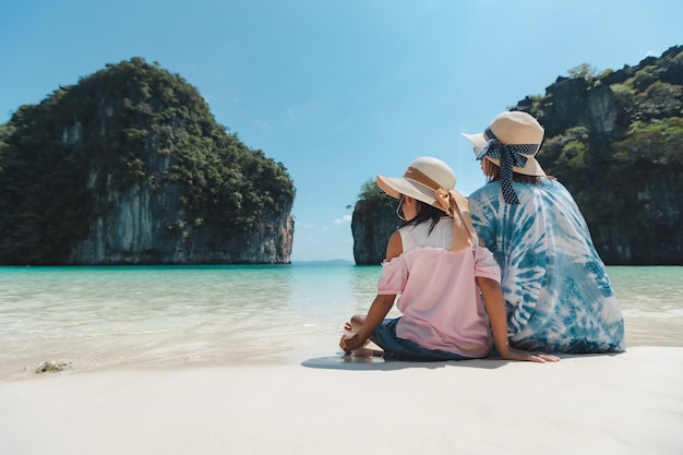 ビーチに座っているアジアの母と子の女の子。