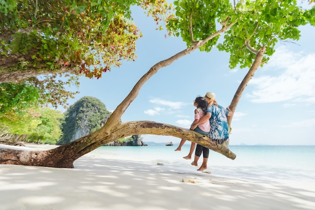 Азиатская девушка матери и ребенка сидя на дереве и наслаждаясь красивой морской природой вместе в их отпуске.