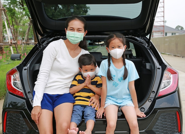 아시아 어머니와 아이들은 코로나바이러스(covid-19)가 발생하는 동안 카메라를 들여다보며 해치백 자동차에 앉아 위생 얼굴 마스크를 착용합니다.