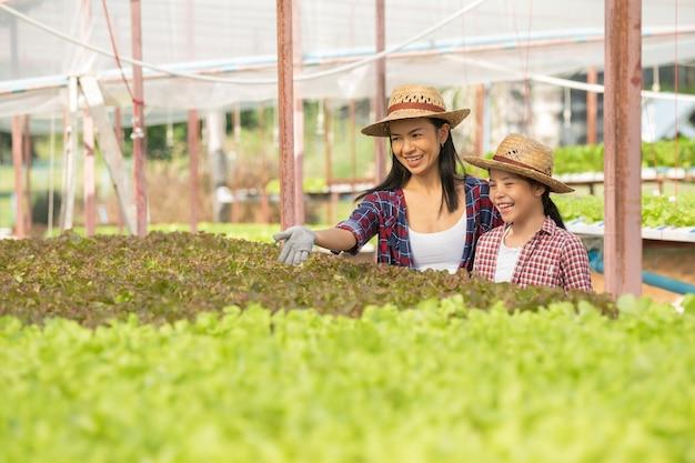 아시아의 어머니와 딸은 농장에서 신선한 수경 재배 야채를 모으고, 개념 정원 가꾸기 및 가정 생활 방식의 가정 농업 어린이 교육을 함께 돕고 있습니다.