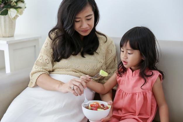 아시아 어머니와 딸이 함께 샐러드를 먹는