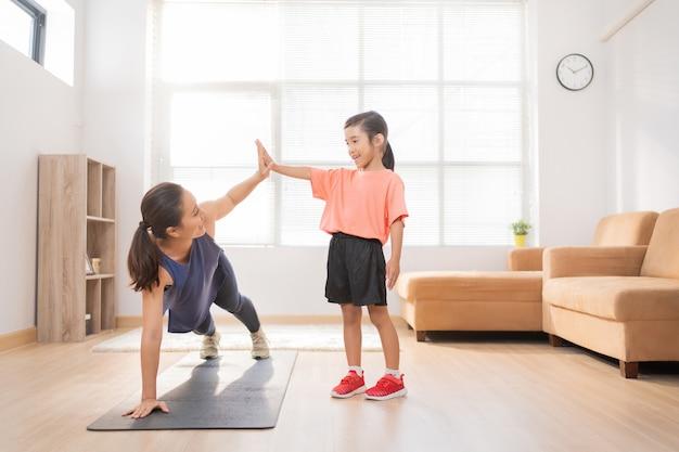 Азиатские мать и дочь делают упражнения дома, они веселятся вместе