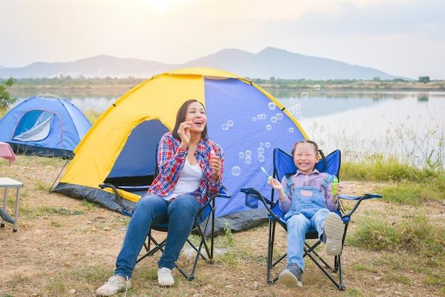 Азиатские мать и дочь веселятся в кемпинге, сидя перед палаткой и дуя мыльный пузырь