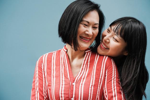 青い背景を持つ屋外で抱き締めるアジアの母と娘