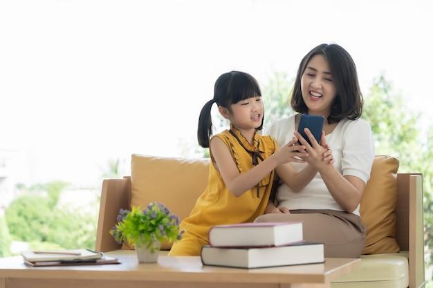 집에서 스마트 폰을 사용하는 아시아 어머니와 딸 아이