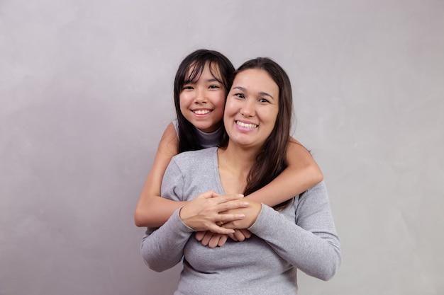 Азиатские мать и дочь на фоне с пространством для текста. концепция дня матери