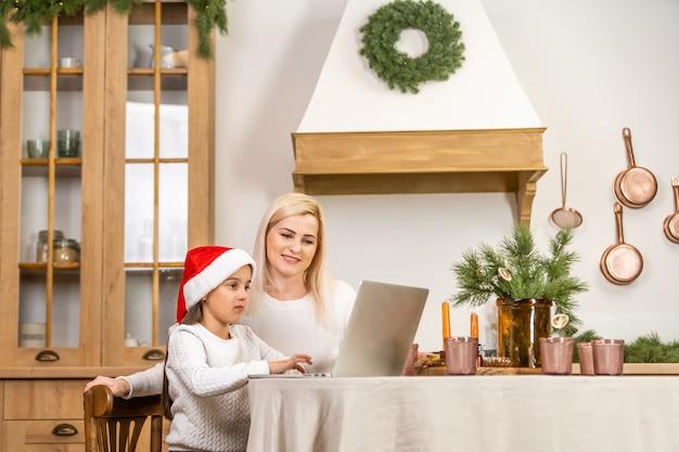 아시아 어머니와 딸이 노트북을 사용하여 화상 통화 facetime 채팅 집에 있는 흰색 방에 크리스마스 트리를 장식하여 아버지와 통신합니다. 웃는 얼굴과 새해 축제를 축하하게 되어 기쁩니다.