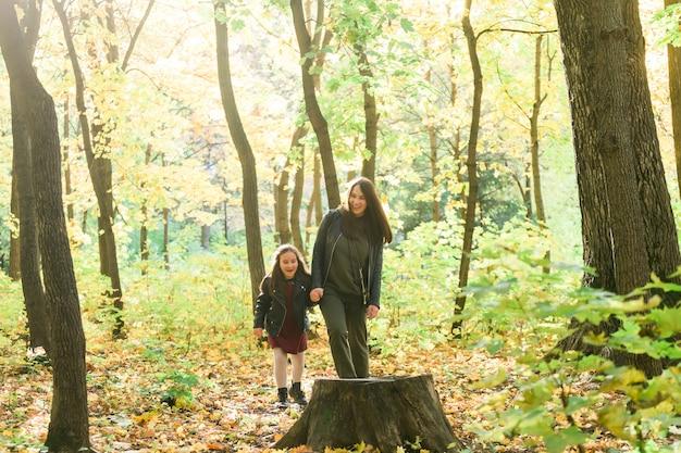 公園で手をつないで歩いているアジアの母と娘彼らは暖かい服を着ているひとり親