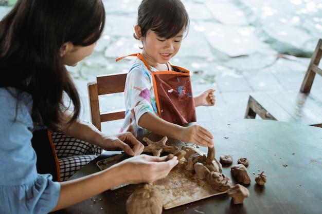 Азиатская мать и дочь работают с глиной