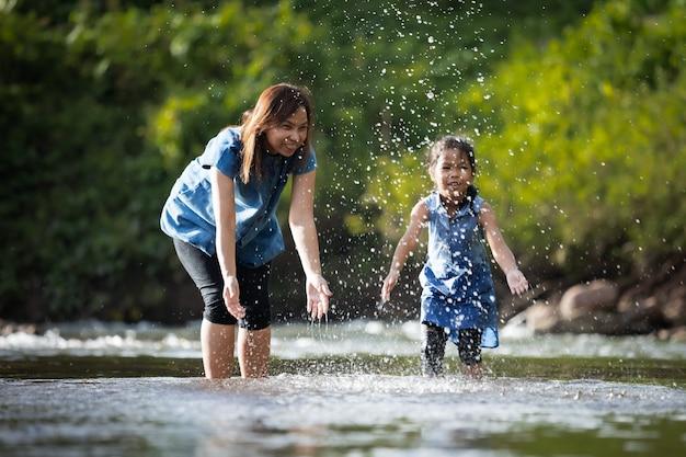 楽しみと一緒に川で遊ぶアジアの母と彼女の子供の女の子