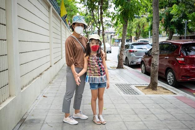 아시아 어머니와 도시에서 걷는 동안 의료 얼굴 마스크를 착용하는 그녀의 딸.