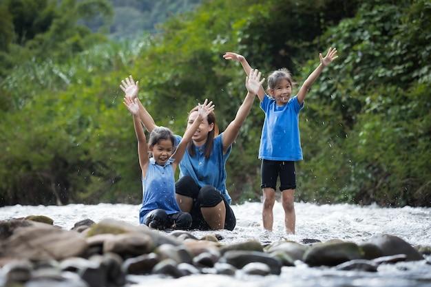 Азиатская мать и ее дочери вместе играют в реке