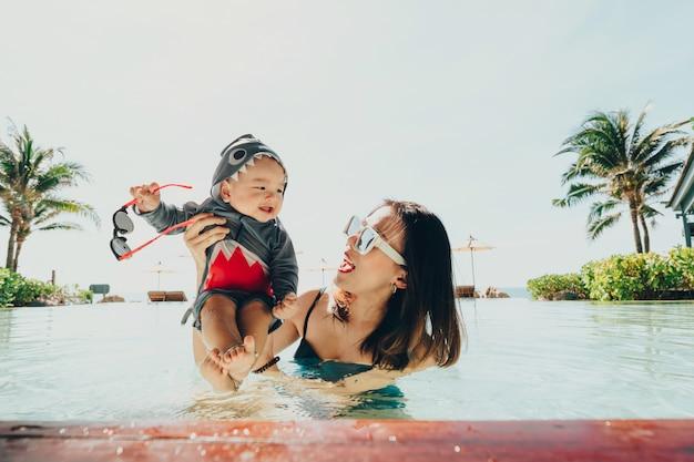 Азиатская мать и маленький сын наслаждаясь плавать в бассейне в летних каникулах.