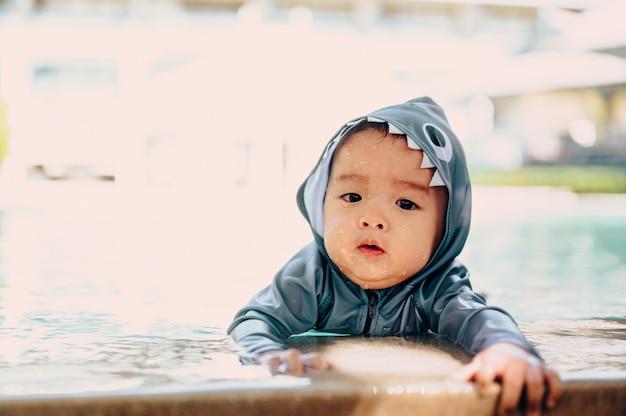 アジアの母と幼い息子が夏休みにプールで水泳を楽しんでいます。