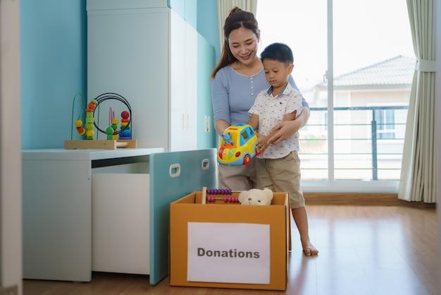 アジアの母と息子は、遊んでいない子供のおもちゃを選び、募金箱を寄付センターに置いています。