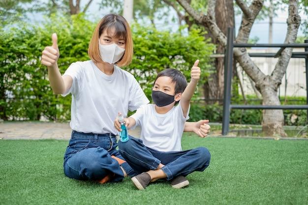 Азиатские мать и сын палец вверх и держат бутылку с распылителем алкоголя, сидя в домашнем саду