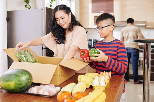 台所のテーブルで新鮮な食料品と箱を開梱するアジアの母と息子