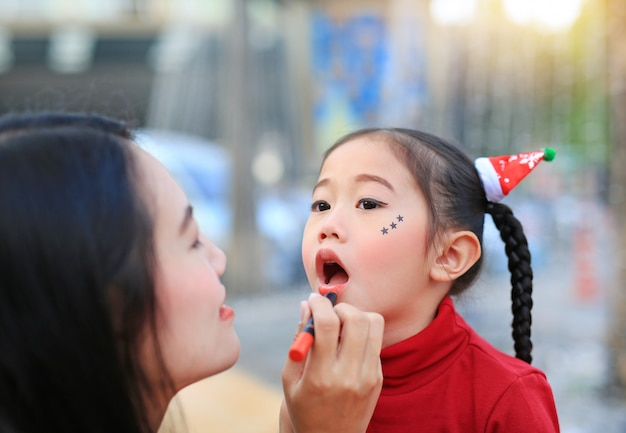 Asian mother applying lipstick over daughter mouth.