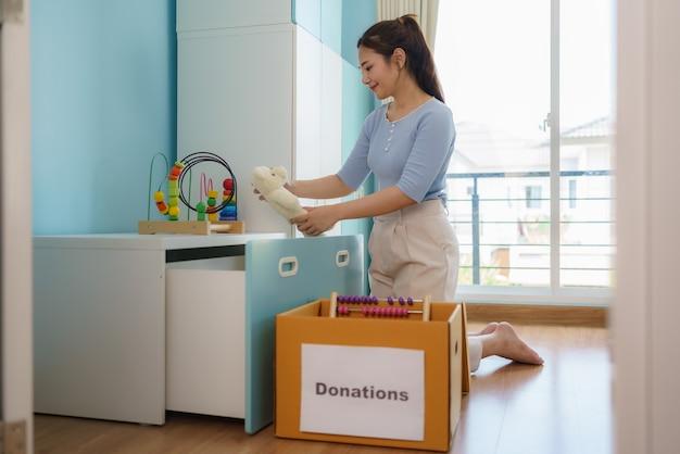 アジアの母親は、遊んでいない子供のおもちゃを選び、募金箱を寄付センターに置いています。
