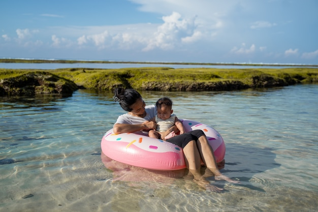 Asian mother and baby ride the rubber ring float on the beach