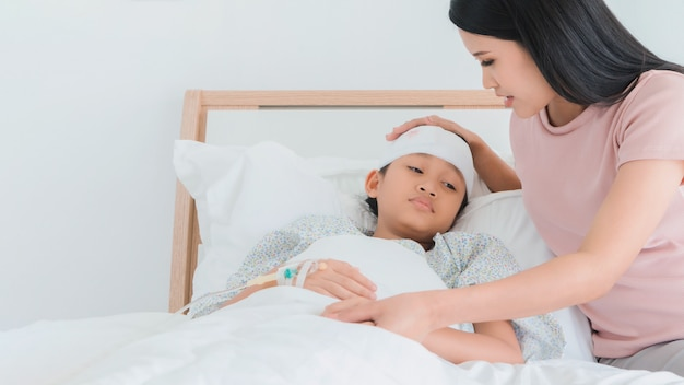 Asian mother caring for daughter injured at head and stay on bed in the hospital.