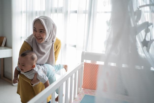 アジアの母は彼女の子供を運ぶ