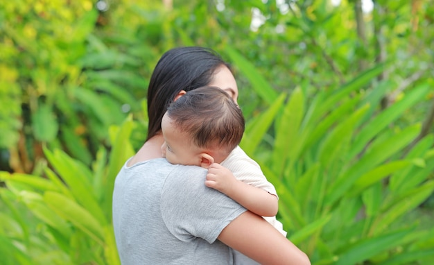 Asian mother carrying her infant baby boy in the green garden.