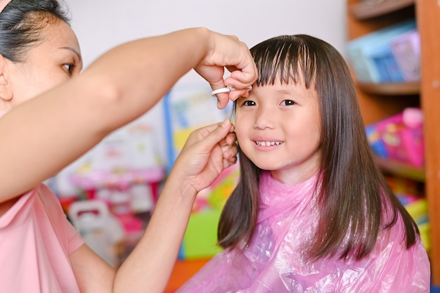 Asian mother cutting hair to her daughter at home