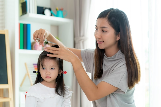 Asian mother cutting hair to her daughter in living room at home