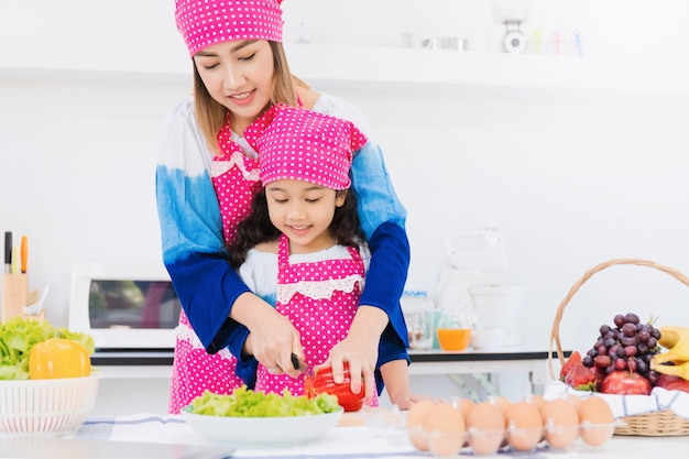 Asian mother and daughter are cooking breakfast together in kitchen room.
