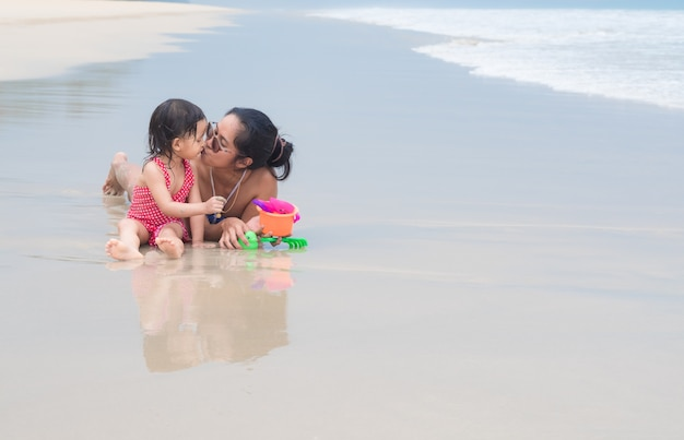 Asian mother and daughter are playing and kissing together on the beach.