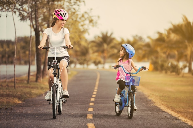 Asian mother and daughter cyclist in the park.