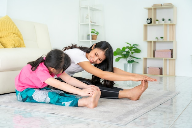 Asian mother and daughter doing fitness exercises in living room at home